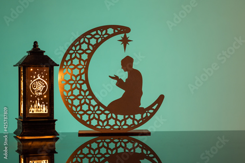 Eid Mubarak concepts with lamp inscribed with arabic text translated to english as Ramadhan is our light., with crescent moon in silhouette