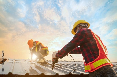 Fotografia Roofer worker in protective uniform wear gloves, using electric screw drill installing iron roof or metal sheet on top of the new roof,Concept of residential building safty under construction