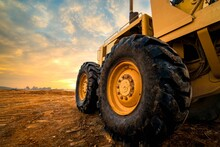 Big Rubber Wheels Of Soil Grade Tractor Car Earthmoving At Road Construction Side.Close-up Of A Dirty Loader Wheel With A Large Tread With Sky Sunset