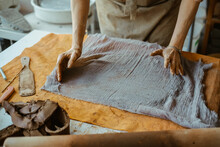 A Woman In An Apron Works With Her Hands With Clay. On The Table Clay, Rolling Pin And A Piece Of Cloth