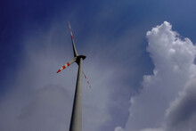 High Wind Turbine With White Cloud And Blue Sky