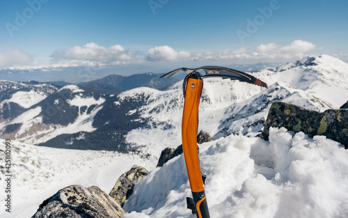 Fototapeta Mountain climbing pick axe in the snow. Ice axe in the snow against the background of the mountains obraz
