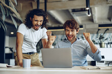 Two Excited Overjoyed Young Businessmen Looking At Laptop Screen Happy To Win Or Recieved Good News