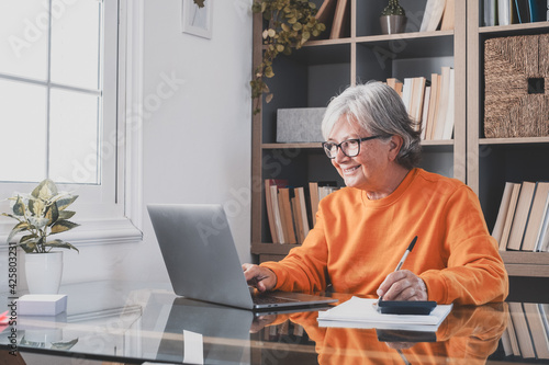 Billede på lærred Happy old caucasian businesswoman smiling working online watching webinar podcast on laptop and learning education course conference calling make notes sit at work desk, elearning concept