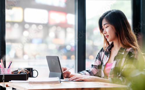 Obraz Young beautiful asian woman using tablet working online while sitting at cafe. - fototapety do salonu