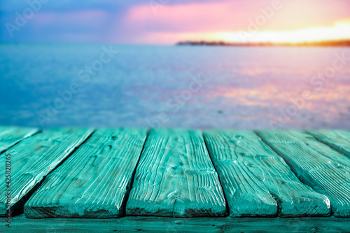 Obraz Sunset on the seashore and wooden table in the evening  - fototapety do salonu