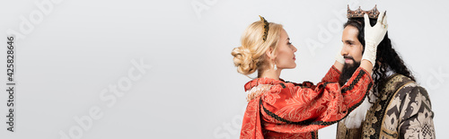 Fotografia blonde queen wearing crown on hispanic king in medieval clothing isolated on whi