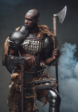 Tribal Authentic Soldier With Axes In Foggy Background Looks Away