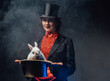 Attractive woman holding a top hat there is a white rabbit in smoke
