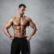 Fitness In Gym, Sport And Healthy Lifestyle Concept. Handsome Athletic Man With Naked Torso Demonstrates His Muscles And Trained Body. Bodybuilder Male Model Posing On Grey Background.