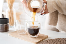 Young Woman Brewing Coffee In Coffee Pot, Pouring Coffee To The Glass