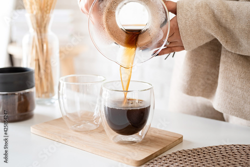 Obraz na plátne Young woman brewing coffee in coffee pot, pouring coffee to the glass