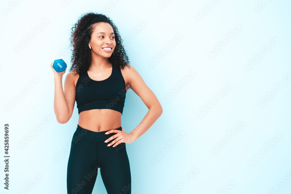 Fototapeta Fitness smiling black woman in sports clothing with afro curls hairstyle.She wearing sportswear. Young beautiful model with perfect tanned body.Female holding dumbbells in studio near blue wall