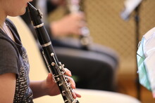 Close-up Of A Baby Girl Playing A Black Clarinet Mouthpiece In Her Mouth Fingers On Silver Flaps In A Music Lesson At School. The Concept Of Children's Music Education And Development