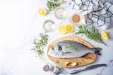Fototapeta Kawa jest smaczna - Raw fresh dorada fish with lemon slices and greens
