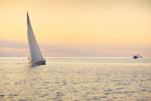 White Sloop Rigged Yacht Sailing In The Baltic Sea At Sunset. Clear Sky After The Storm, Golden Sunlight. Flying Swan Close-up. Transportation, Travel, Cruise, Sport, Recreation, Racing, Regatta