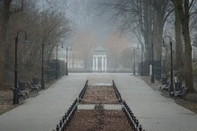 Empty Street (alley) In A City Park. Lanterns, Benches, Gazebo In The Background. Mighty Trees In A Fog, Overcast Day. Walking, Cycling, Recreation, Landscaping Concepts. Spring Landscape, Cityscape