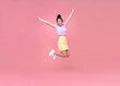Happy Asian woman smiling and jumping while celebrating success isolated over pink background.