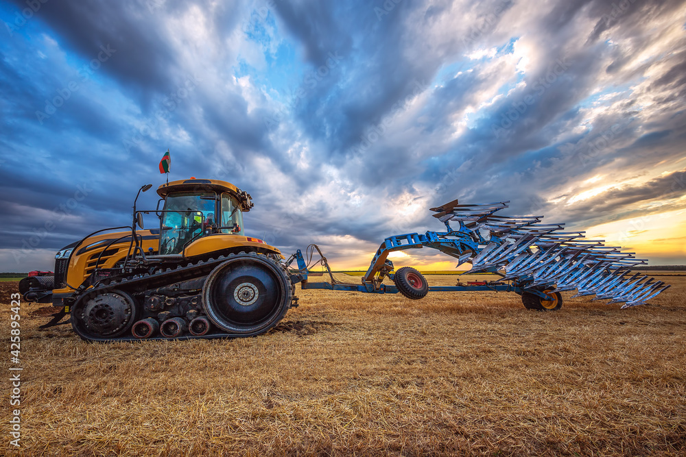 Fototapeta Tractor plowing the fields