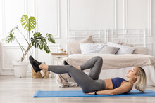 Concentrated Beautiful Woman In Stylish Sportswear Working Out At The Morning On Blue Yoga Mat. Athletic Blonde-hair Girl Is Training At Home, Doing Criss Cross Exercises. Healthy Lifestyle Concept