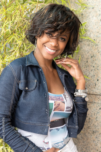 Tela face of afro descendant woman smiling, with short wavy hair, wears makeup and je