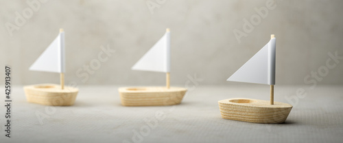 Obraz na plátně Conceptual image of three simple little wooden sailboats with sails over a grey