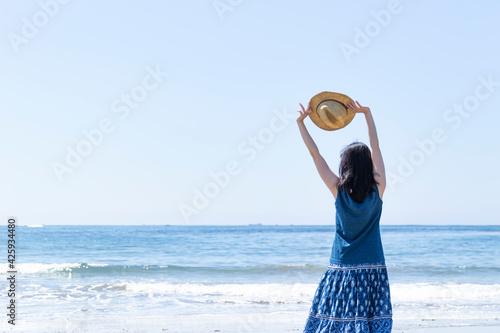 麦わら帽子を持ってストレッチをしながら海を眺める女性