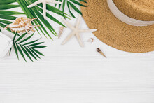 Tropical Palm Leaves, Straw Hat, Starfish, Seashells On White Wooden Background. Trendy Tropical Pattern. Fashion Clothing And Accessories. Flat Lay, Close Up. Summer, Vacation, Holidays Concept.
