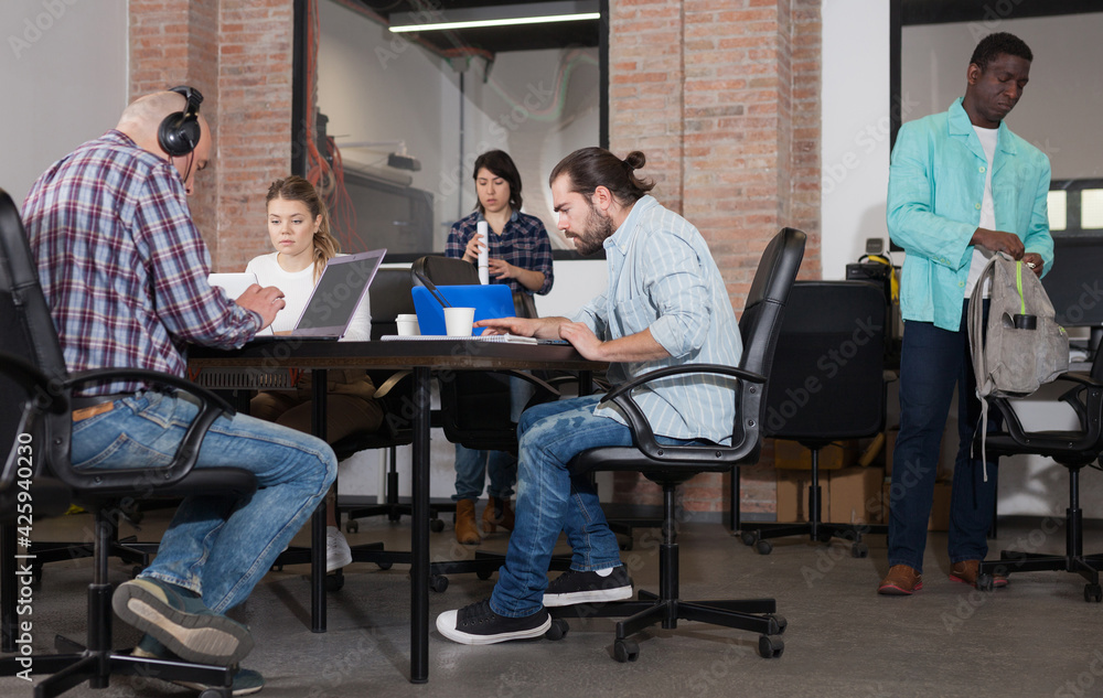 Fototapeta Multiethnic startup business team working on new project in loft style coworking space..