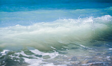 Turquoise Blue Sea Wave Crashes On A Pebble Shore, Nature Background And Texture