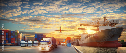 Fototapeta Container truck in ship port for business Logistics and transportation of Container Cargo ship and Cargo plane with working crane bridge in shipyard at sunrise, logistic import export  concept obraz