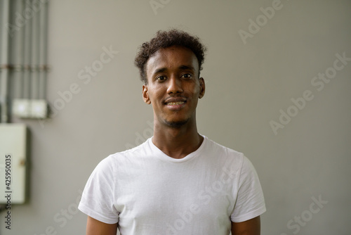 Fototapeta Portrait of handsome black African man with cool attitude against plain wall background obraz