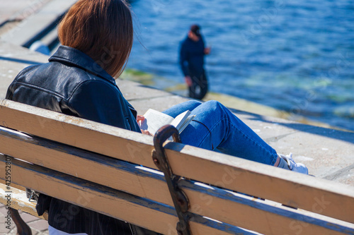 Young girl on the embankment reads a book, vacation at the seaside, student vaca Wallpaper Mural