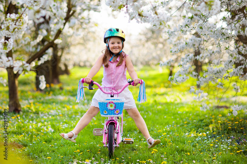 Fototapeta Kids on bike in spring park. Girl riding bicycle. obraz
