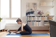 Woman Practicing Yoga At Home Through Live Video