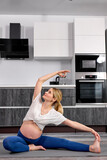caucasian pregnant woman sits on fitness mat at home, doing exercises for warm-up legs