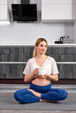 Pregnant happy fitness person enjoy cup of water or tea while sitting on floor after yoga practice at home