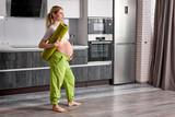 side view on pregnant lady with big tummy looking at side, holding fitness mat in hands