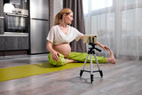 Pretty Blonde Caucasian Pregnant Woman Do Yoga Exercises Watching Video Online