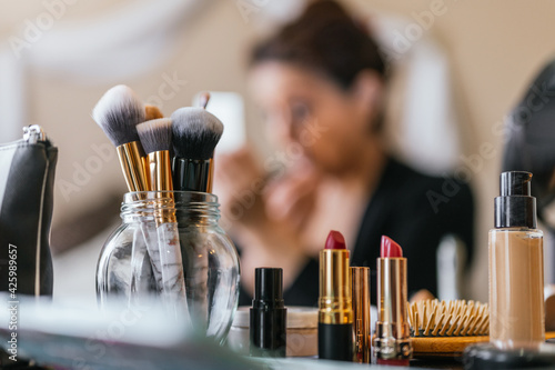 Fotografia Lipsticks on a wooden table and in the background a woman putting on makeup