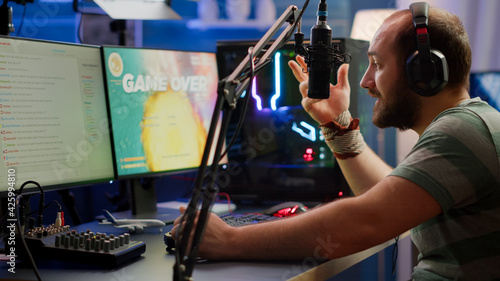 Fotografia Nevous streamer losing videogame, game over for man cyber playing online space shooter games with headset