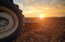 Agriculture Use Tractor Plowing Field.Wheels In Mud Field And Sunset Sky Backround. Cultivated Field.Agronomy Farmer Use Tractor Preparing Land With Seedbed Cultivator.Agricultural Works At Farmland.