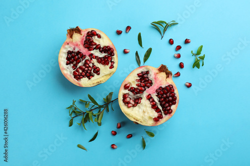 Flat lay composition with ripe pomegranate on light blue background