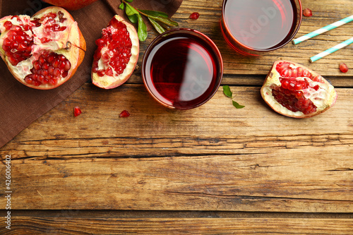 Freshly made pomegranate juice on wooden table, flat lay. Space for text