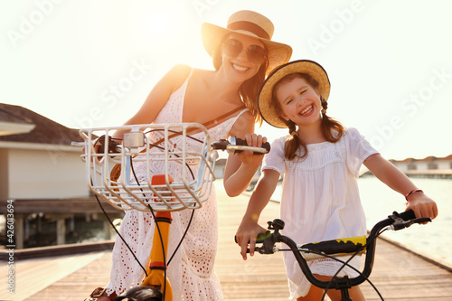 Canvas Cheerful mother and daughter on bicycles enjoying summer holidays