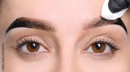 Photo Beautician wiping tint from woman's eyebrows on white background, closeup