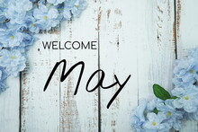 Welcome May Text And Blue Flower Decoration On Wooden Background