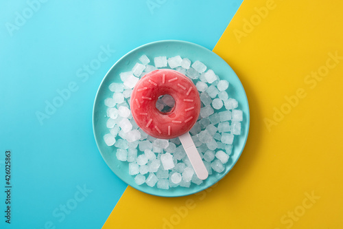 Photo Strawberry donut popsicle  and crushed ice on yellow and blue background