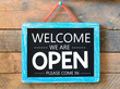 Welcome we are open words written on a chalkboard.