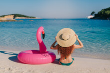 Young Red-haired Woman In A Swimsuit And Hat Sits On The Beach Next To An Inflatable Flamingo On A Sunny Day.
